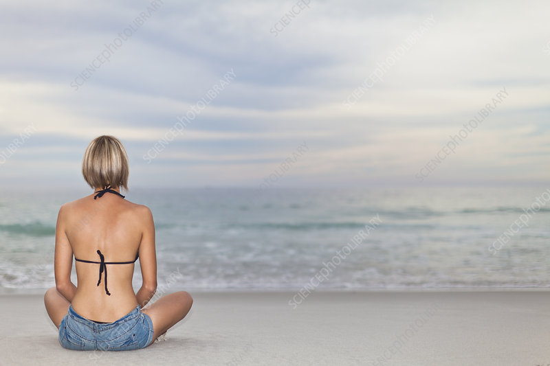 Woman sitting cross legged on beach