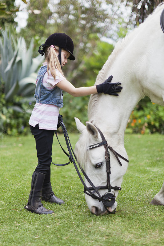 Girl petting grazing horse in park