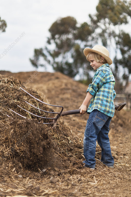 Boy using pitchfork in haystack