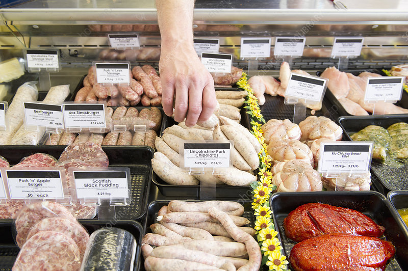 Butcher reaching for sausages in case