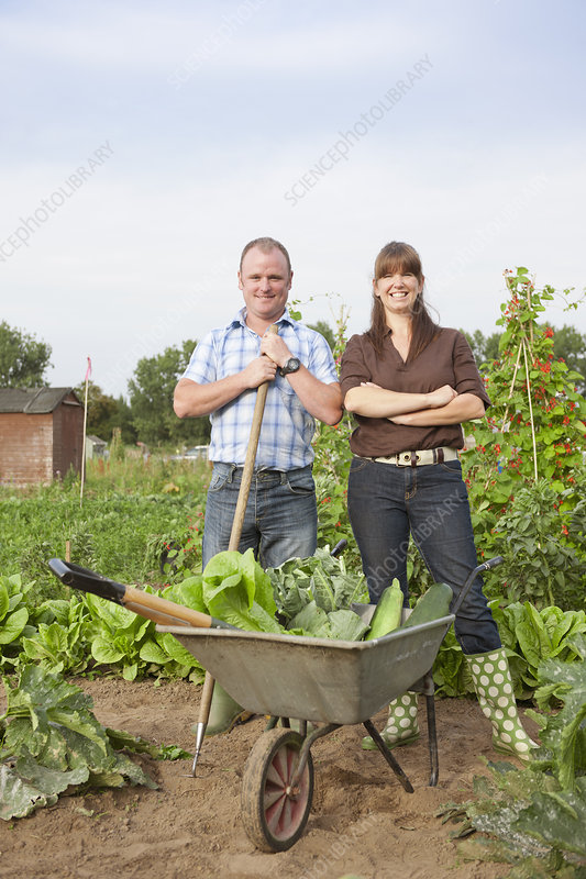 Couple with wheelbarrow with vegetables