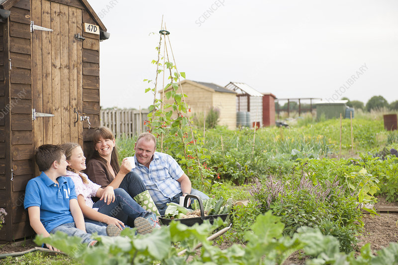 Family relaxing near garden shed