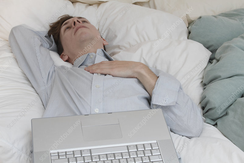 Businessman with laptop laying on bed