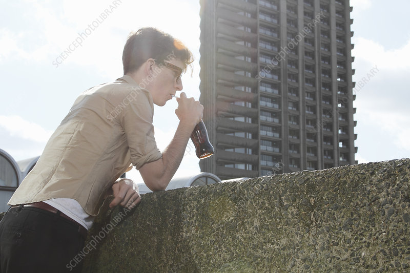 Man drinking soda on balcony