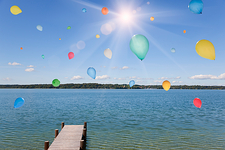 Balloons floating over still lake