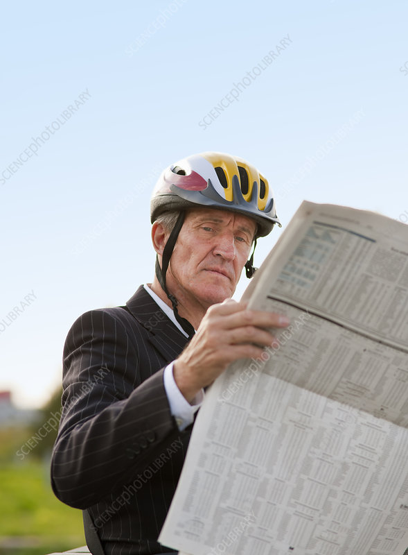 Businessman in bicycle helmet reading