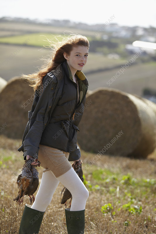 Teenage girl carrying game birds