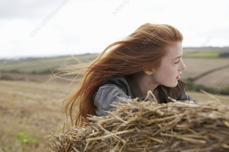 Teenage girl resting on haybale
