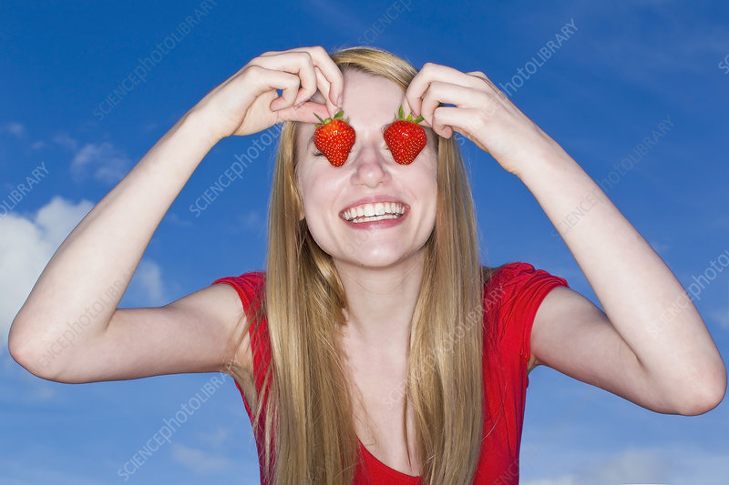 Woman holding strawberries over eyes