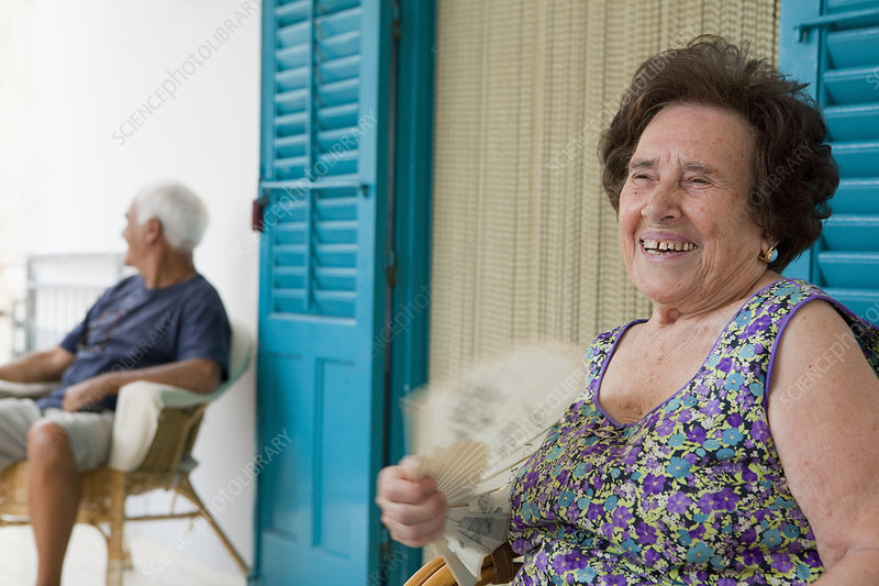 Older woman fanning herself outdoors
