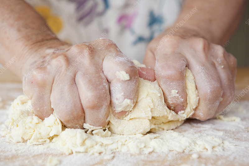 Close up of older woman kneading dough