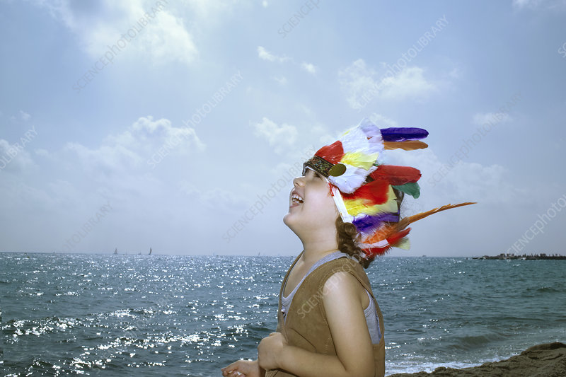 Toddler in Indian headdress on beach