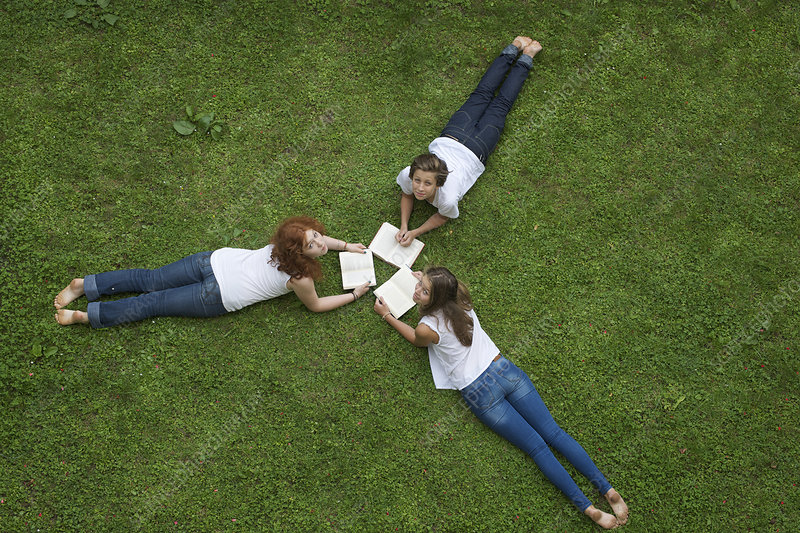 Teenagers laying in grass reading books