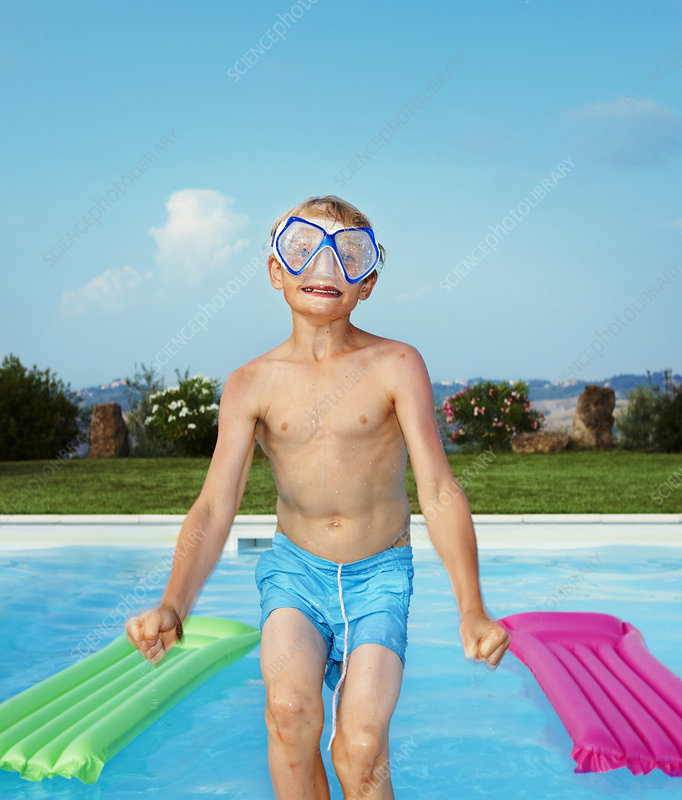 Boy in mask jumping into swimming pool