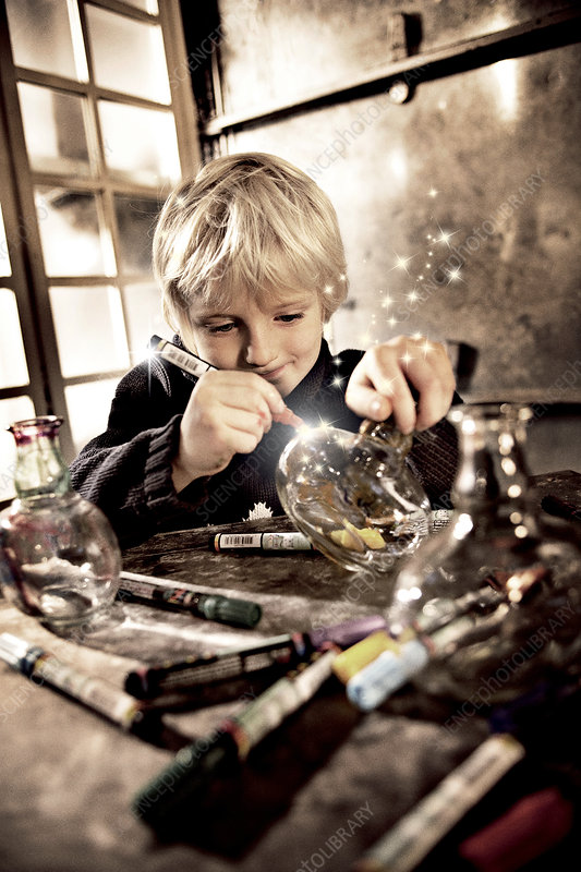 Boy drawing on glass jar with light