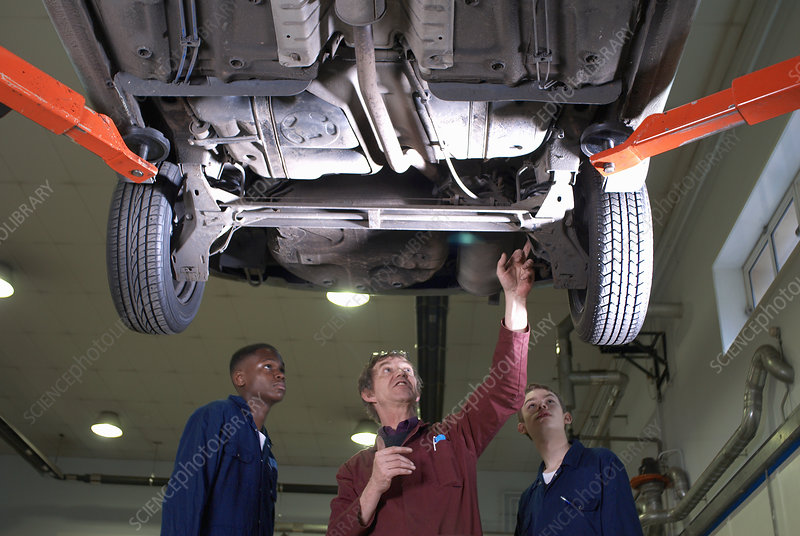 Teacher helping students with car engine