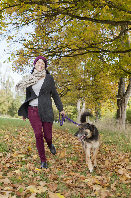Smiling woman walking dog in park
