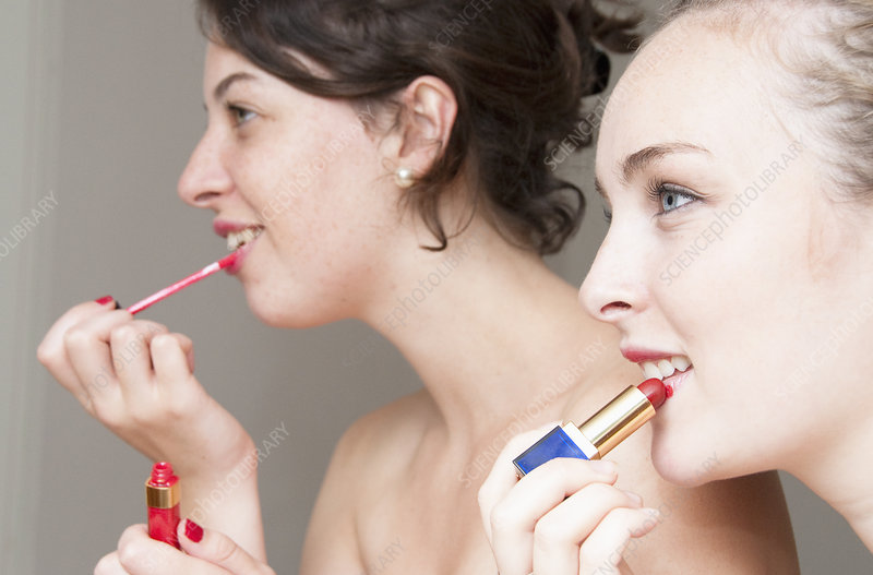 Teenage girls applying makeup