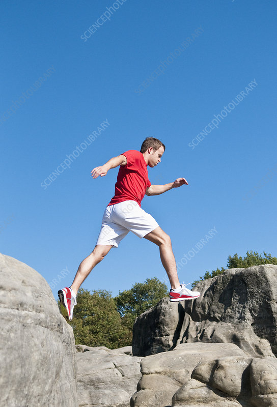 Rock climber jumping between rocks