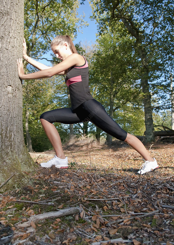 Runner stretching against tree in park