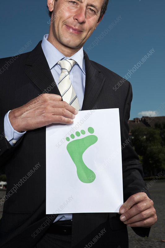 Businessman holding footprint on paper