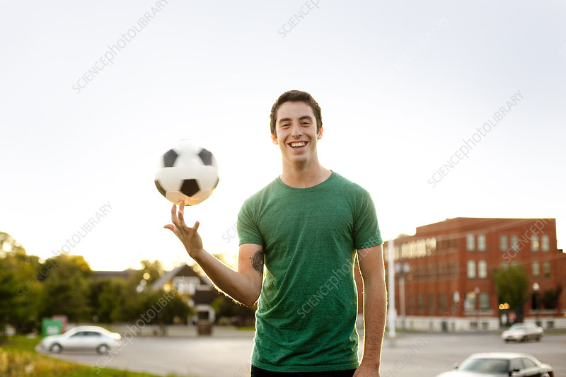Man spinning soccer ball on finger