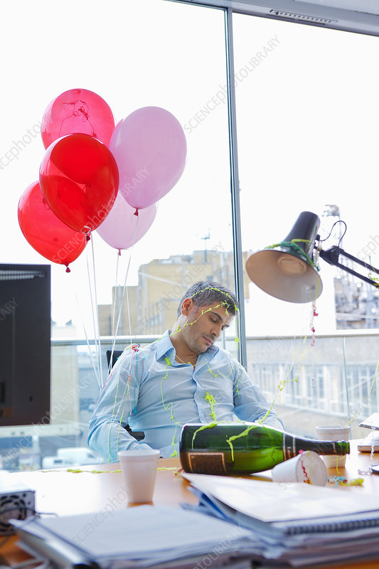 Businessman asleep at desk after party