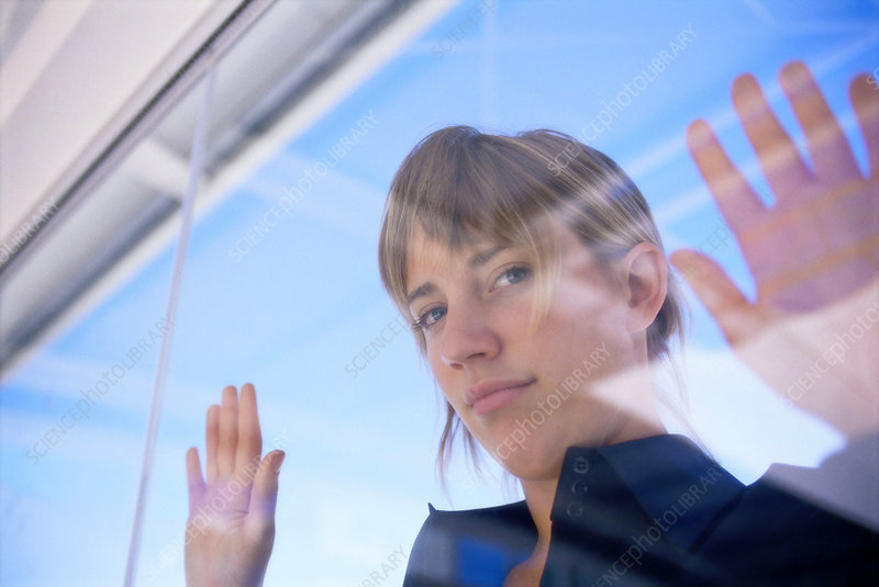 Woman peering in through glass window