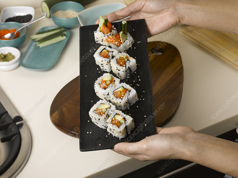 Woman holding tray of sushi
