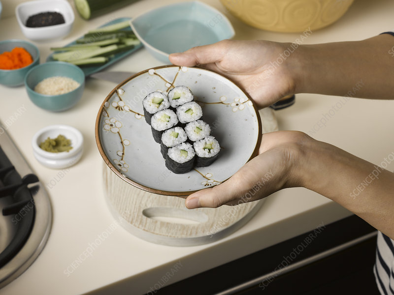 Woman holding plate of sushi