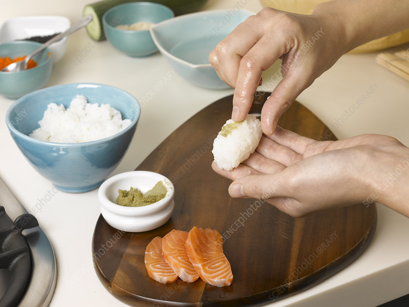 Woman preparing sushi at table