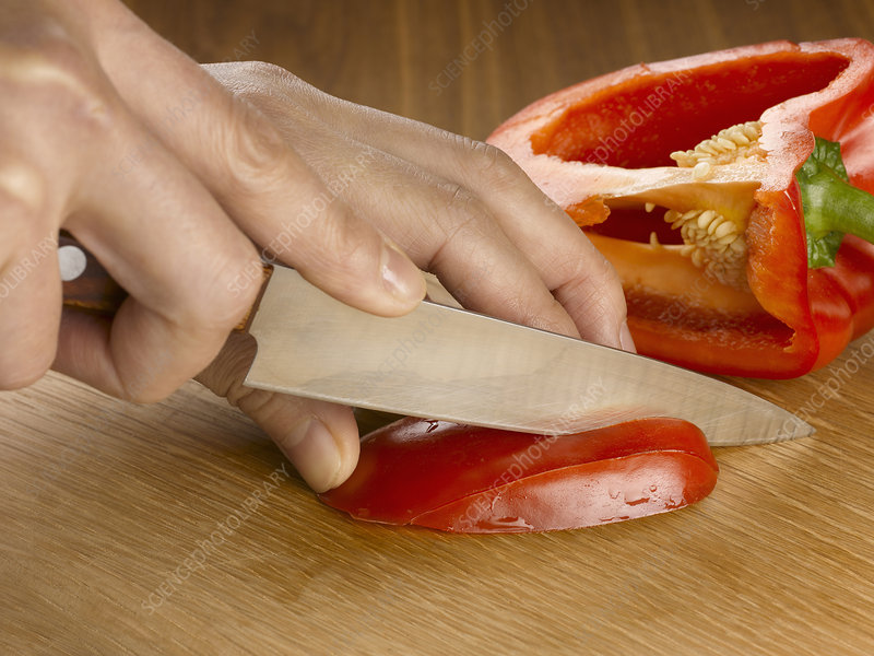 Close up of hands cutting bell pepper