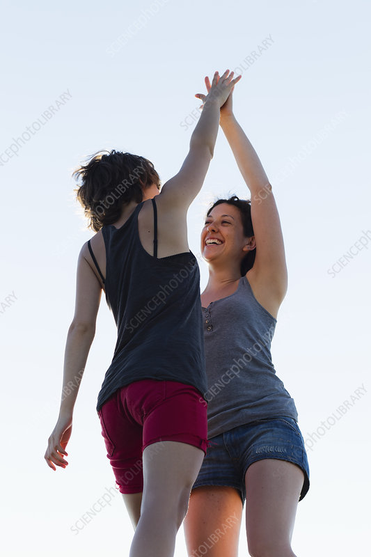 Women high-fiving outdoors
