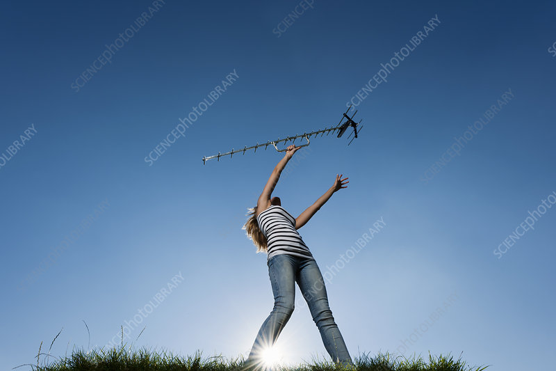 Woman holding up antenna outdoors