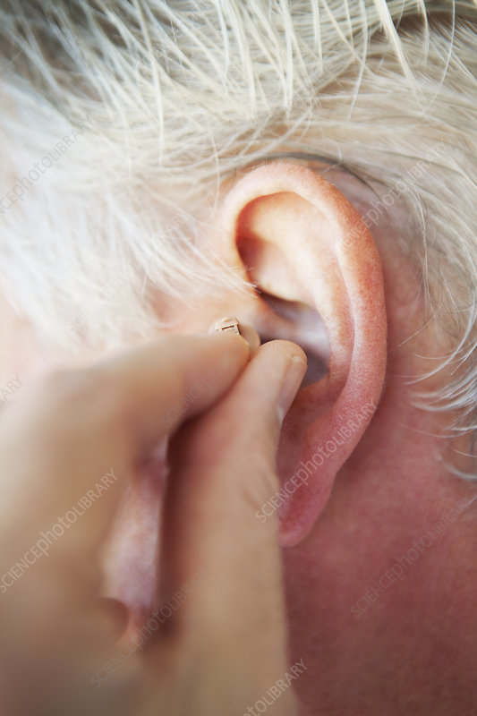 Older person inserting hearing aid