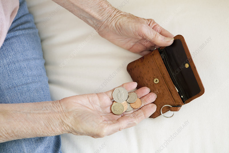 Close up of older woman counting coins