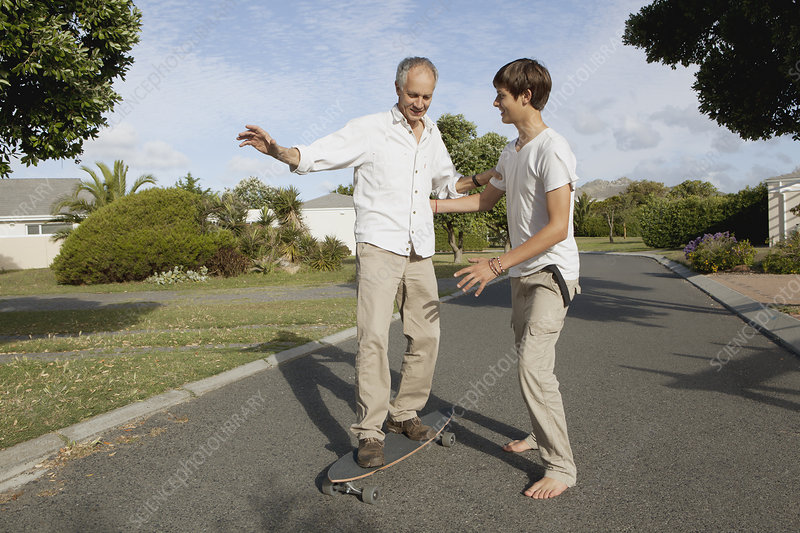 Father and son playing with skateboard