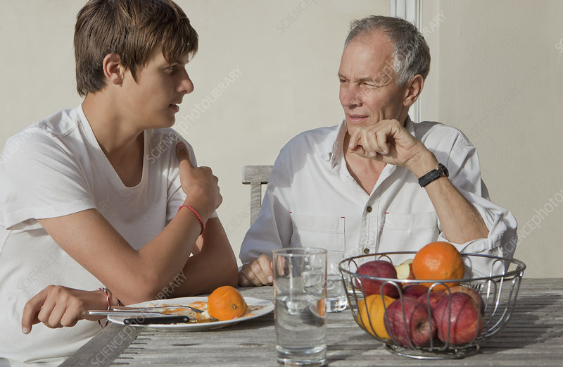 Father and son eating fruit outdoors