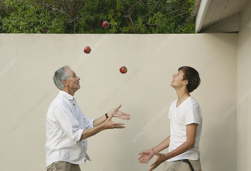 Father teaching son to juggle outdoors