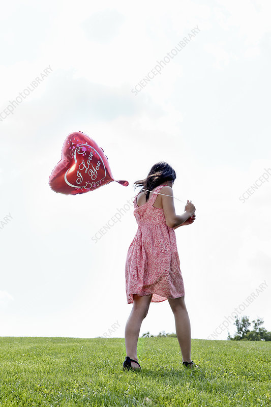 Teenager carrying heart-shaped balloon