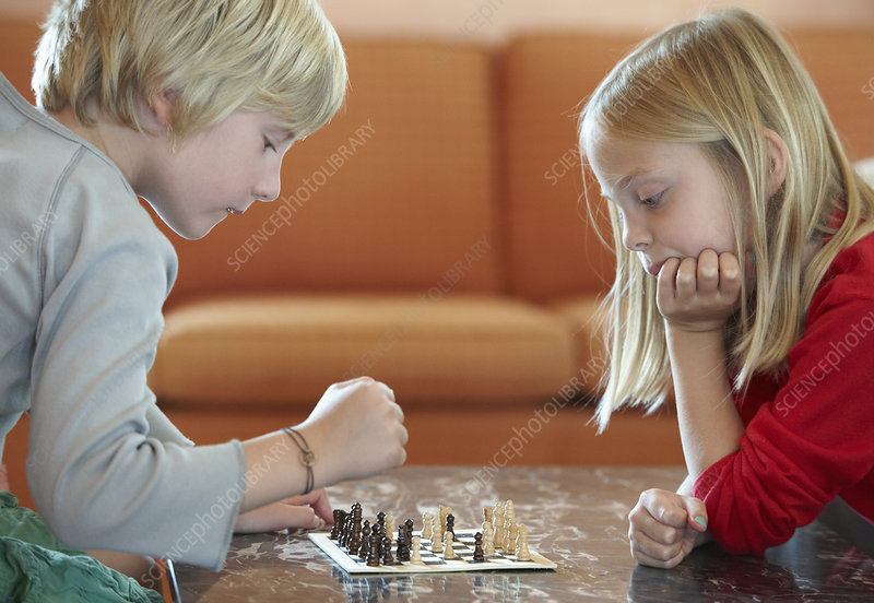 Children playing chess in living room