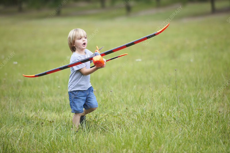 Boy playing with toy airplane outdoors