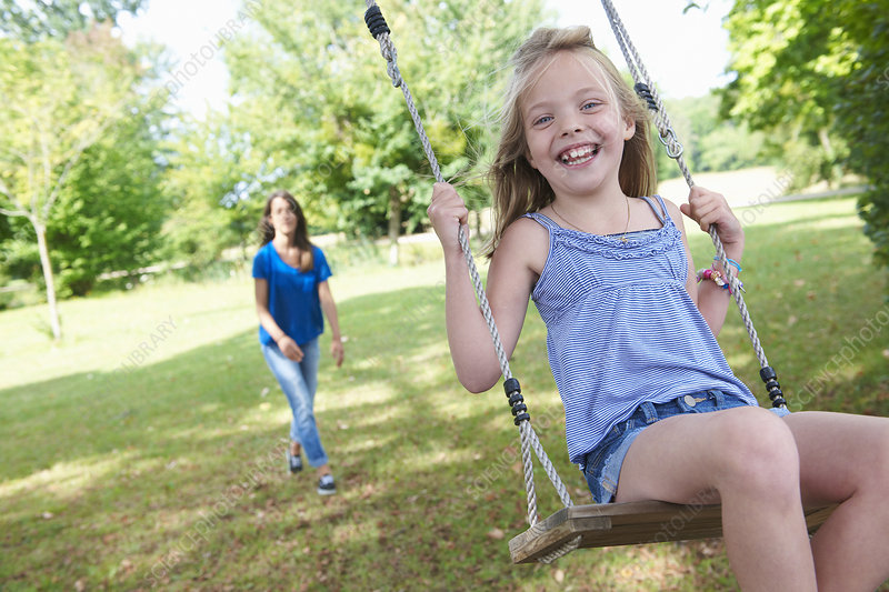 Girl playing on swing in backyard