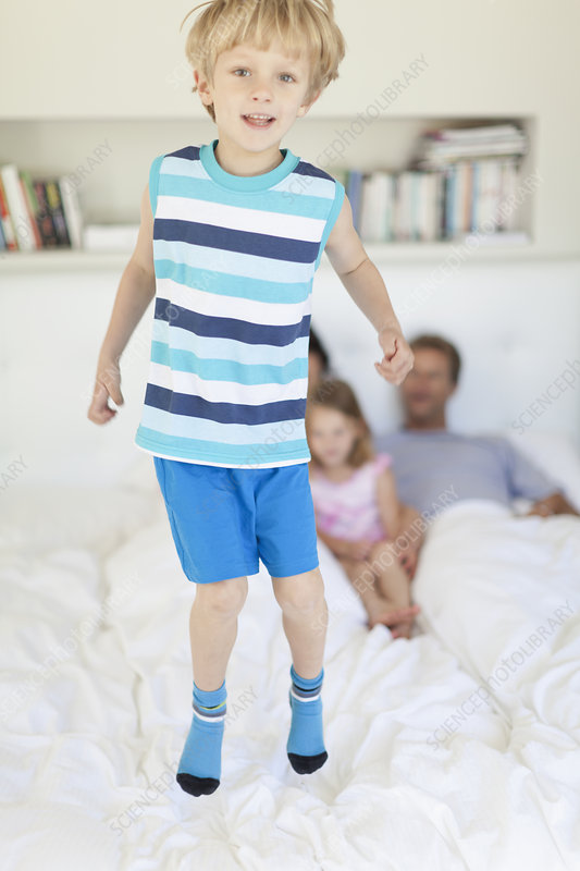 Boy jumping on parents' bed