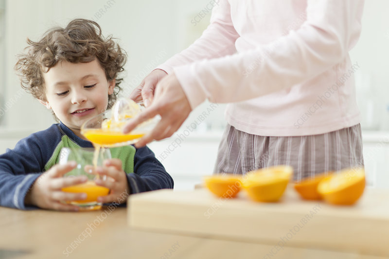 Mother pouring orange juice for son
