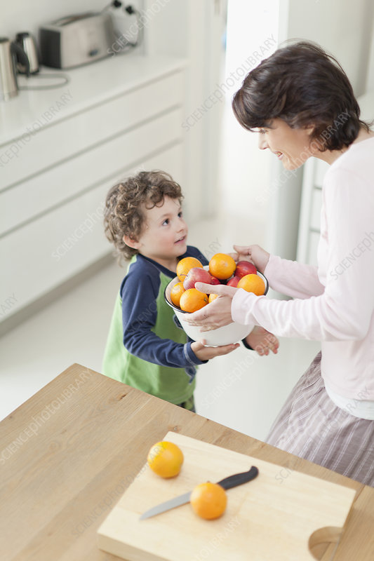 Mother and son with fruit in kitchen