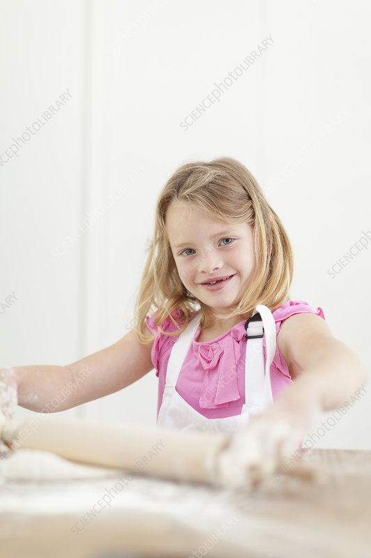 Girl rolling out dough in kitchen