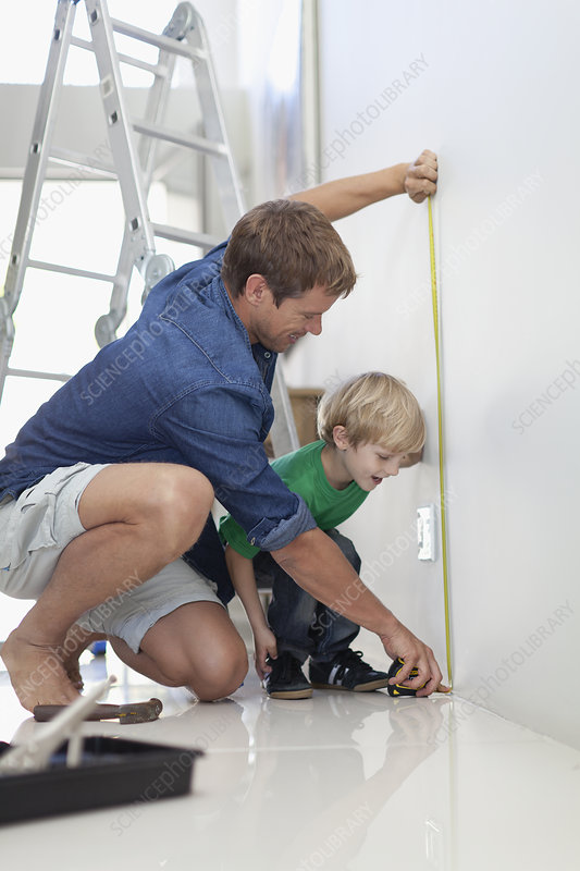 Father and son measuring wall