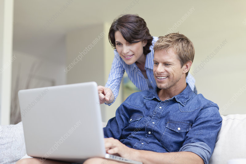 Couple using laptop together on couch