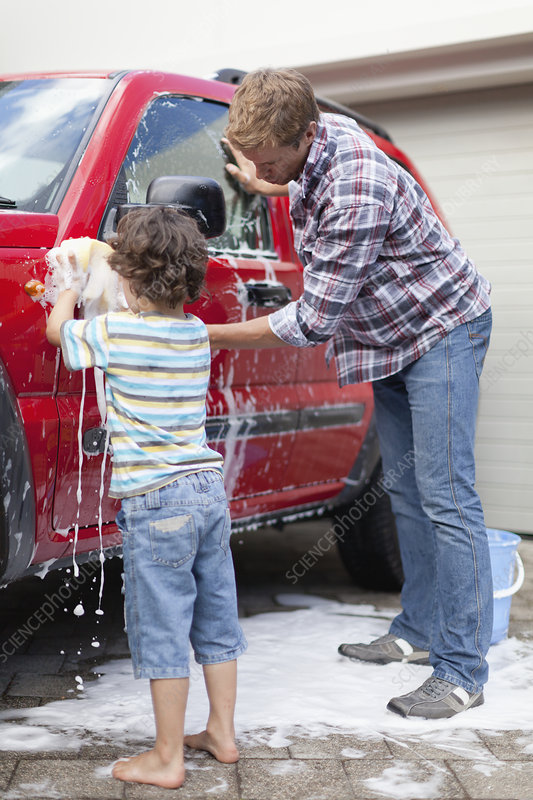 Father and son washing car together